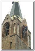 renowacja elewacji z starej cegły technikami alpinizmu przemysłowego, alpinista w trakcie prac na wieży kościoła